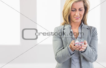 Thoughtful realtor standing looking and presenting a mini model house
