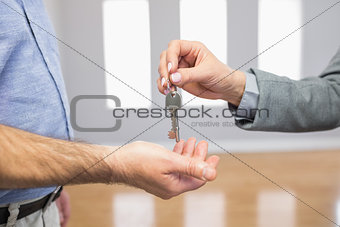 Estate agent giving house key to customer