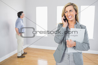 Cheerful realtor calling someone with her mobile phone