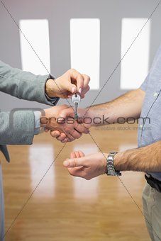 Close up of a handshake and a key delivery