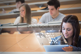 Focused pretty student working on her futuristic tablet