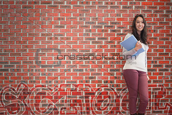 Smiling student holding notebook posing