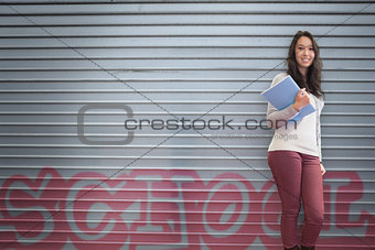 Happy student holding notebook posing