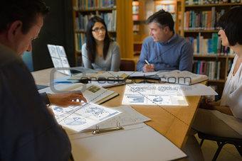 Focused mature students working on their digital tools