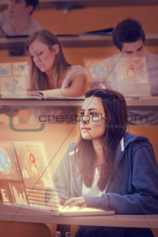 Concentrated pretty student working on her futuristic laptop