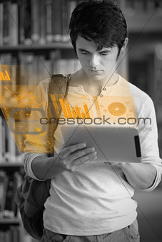 Focused handsome student working on his futuristic tablet