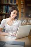 Smiling student analysing graphs on her digital laptop