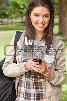 Happy young woman working on her futuristic smartphone
