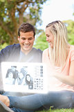 Smiling young couple watching photos on digital interface