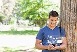 Smiling handsome student using his digital smartphone