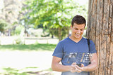 Cheerful handsome student using his digital smartphone