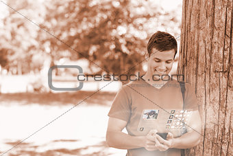 Cheerful handsome student using his digital phone