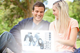 Smiling young couple watching photos together on digital interface