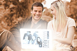 Happy young couple watching photos together on digital interface