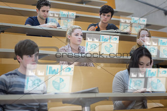 Focused students in lecture hall working on their futuristic tablet