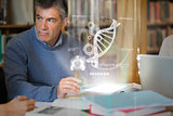 Mature student using futuristic hologram to learn biology from tablet pc