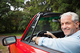 Smiling handsome man driving red cabriolet