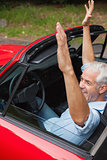 Cheerful handsome man enjoying his red cabriolet