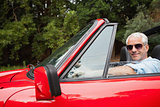 Cheerful handsome man enjoying his red convertible