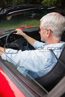 Handsome man driving his red convertible