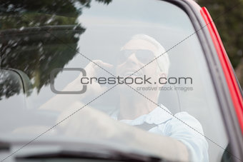 Smiling handsome man in red convertible having phone call