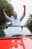 Cheerful mature man enjoying his red convertible