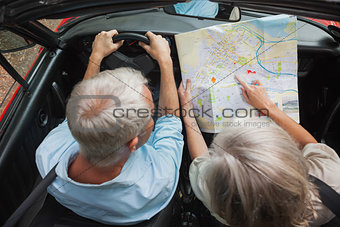 Overhead view of mature couple reading map
