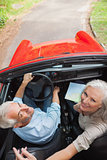 Mature couple in red convertible looking at camera