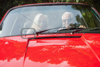 Smiling mature couple in red cabriolet