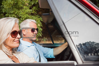 Side view of mature couple driving red cabriolet