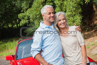 Happy mature couple posing by their red convertible