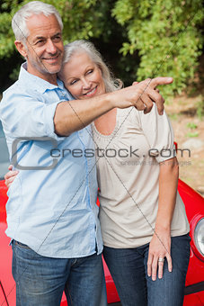 Smiling mature couple posing by their red convertible