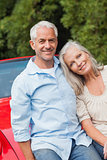 Cheerful mature couple sitting on their red convertible
