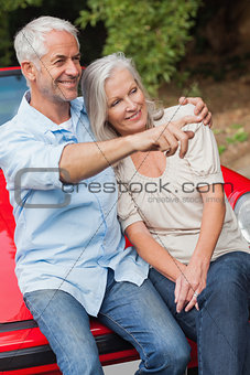 Smiling mature couple sitting on their red convertible