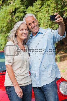 Smiling mature couple taking pictures of themselves