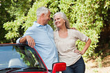 Smiling mature couple hugging by their red cabriolet