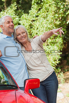 Mature couple leaning against their red cabriolet