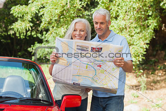 Smiling mature couple reading map