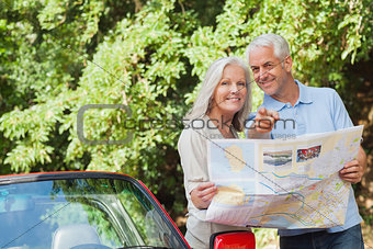 Smiling mature couple looking for direction