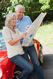 Cheerful mature couple reading map together