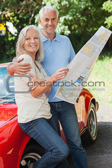 Happy mature couple reading map together