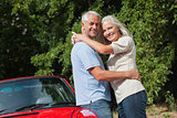 Smiling mature couple hugging against their red cabriolet