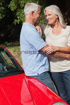 Cheerful mature couple hugging against their red cabriolet