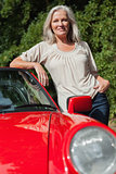 Smiling mature woman leaning against her red cabriolet