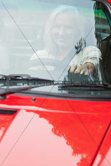 Smiling mature woman driving red cabriolet