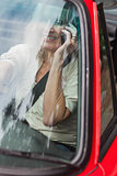 Smiling mature woman on the phone driving red cabriolet