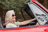 Happy mature woman with sunglasses driving red convertible