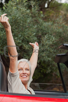 Happy mature woman enjoying her red convertible