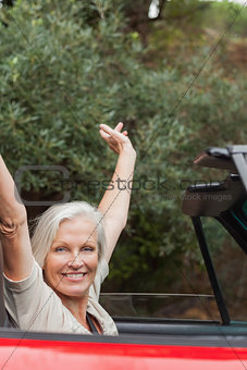 Cheerful mature woman enjoying her red convertible