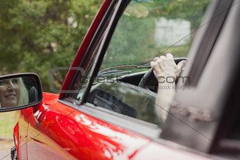 Cheerful mature woman driving convertible